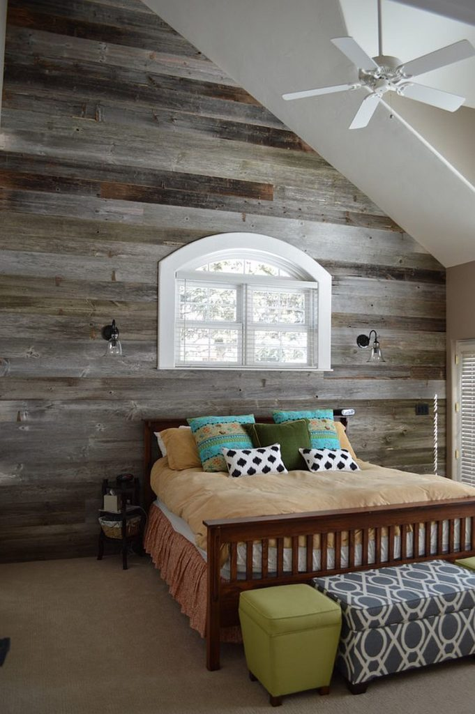 Grey washed reclaimed wood is used in this loft room for a traditional barn charm. The window sits just above the double bed.