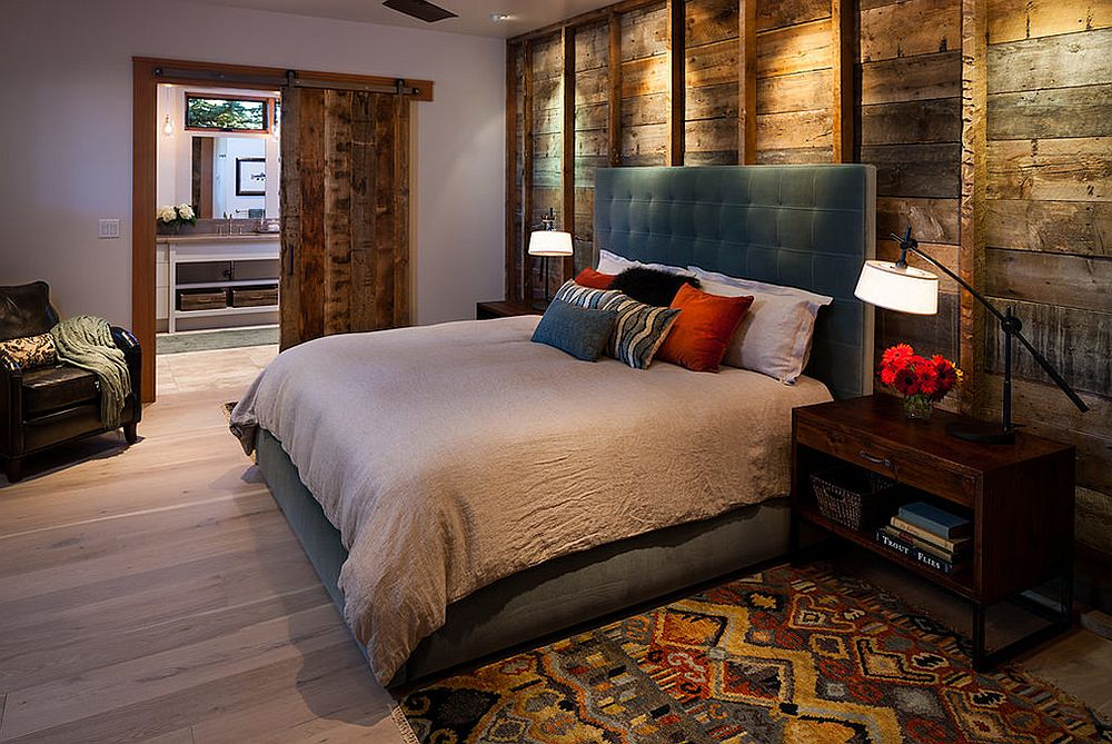 Reused wood as bedroom wall cladding with exposed vertical support frames to divide the wall and downlight for effect