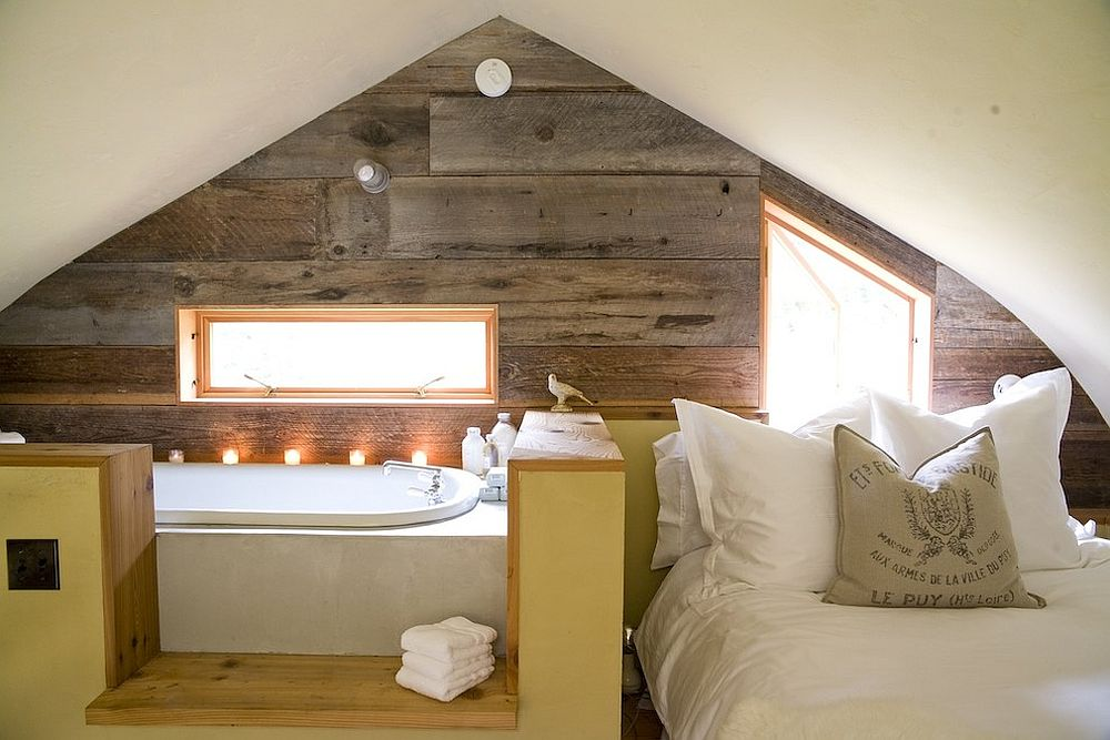 Small loft room with savvy use of space with a wooden effect wall that unifies both the open plan bedroom and bathroom