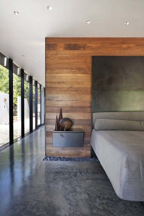 The room feels dark because of the dark gray floor but there is plenty of light from the floor to ceiling glass doors. The wooden feature wall acts to break and divide the open plan living space. A gap exists where the floor meets the feature wall. This is filled with large dark pebbles.