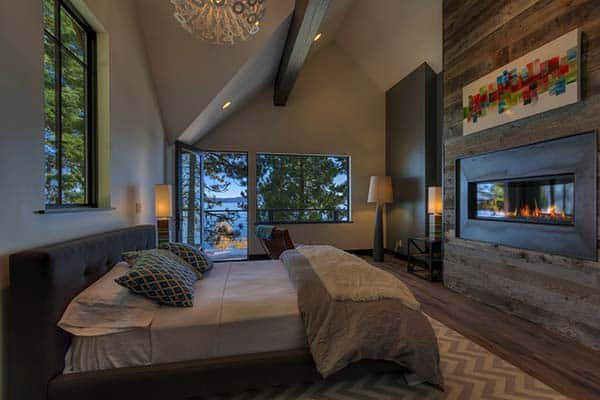 Standing out from the rest, the wooden feature wall with built-in fire place sits opposite the bed.