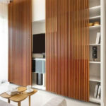 This wooden decorative wall paneling also works to hide the shelves and media unit