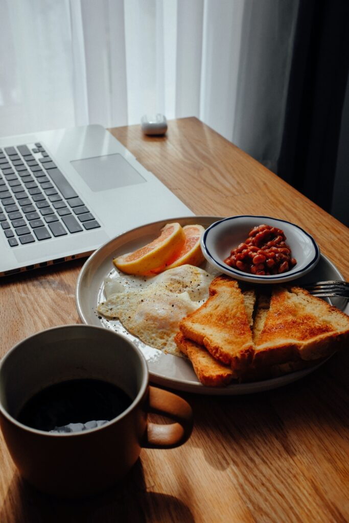 plate of food on desk next to computer